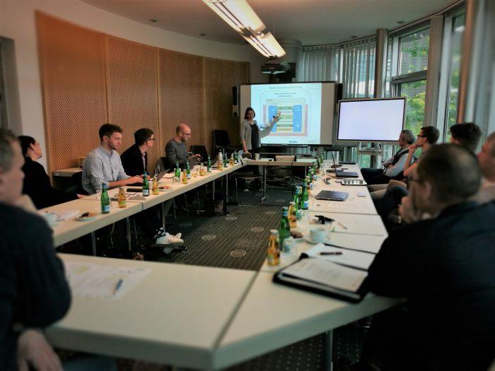 Bild von der Beiratssitzung. Man sieht die Beiratsmitglieder an Tischen sitzen und vorne steht Frau frohn und beschreibt ein Schaubild zu der App.